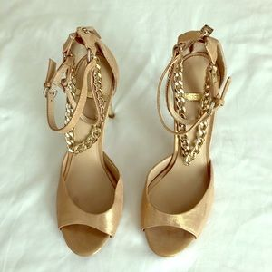Soft gold heels with connected ankle bracelets.